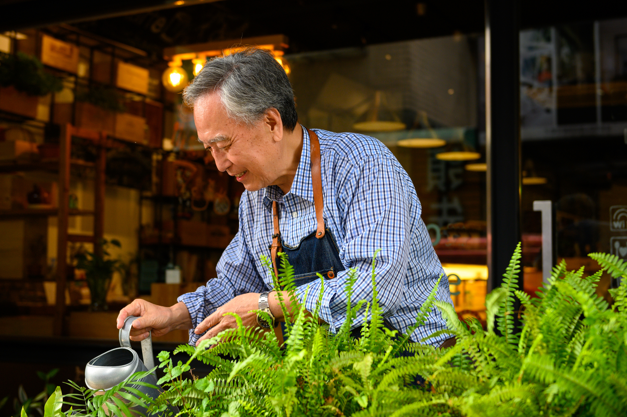 senior owner watering plants at restaurant